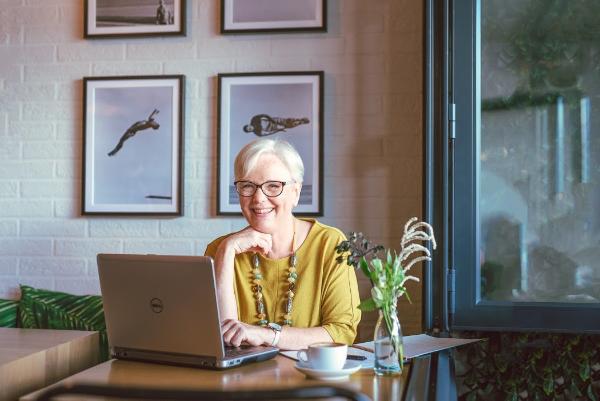 Linda Ward working with laptop & smiling